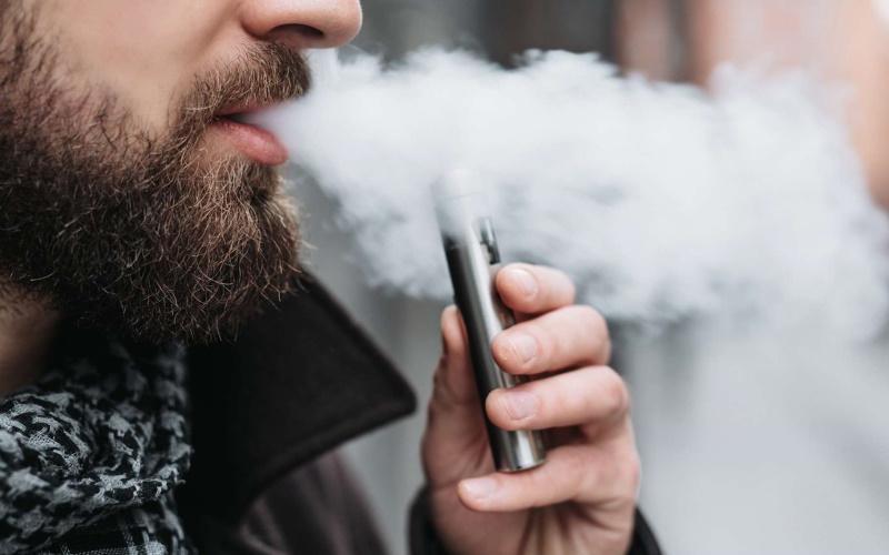 ανδρας ατμίζει ηλεκτρονικό τσιγάρο