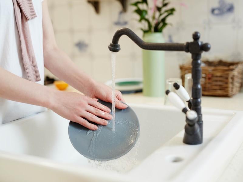 Χέρι ξεπλένει πιάτο κάτω από βρύση