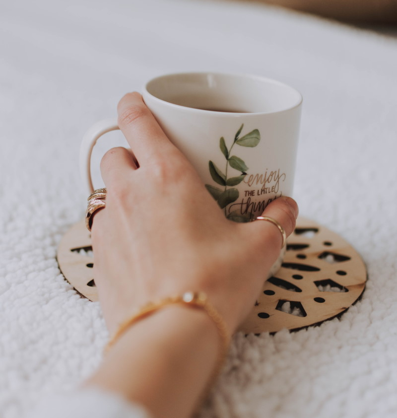 Βραχιόλια και δαχτυλίδια σε γυναικείο χέρι που ακουμπάει κούπα