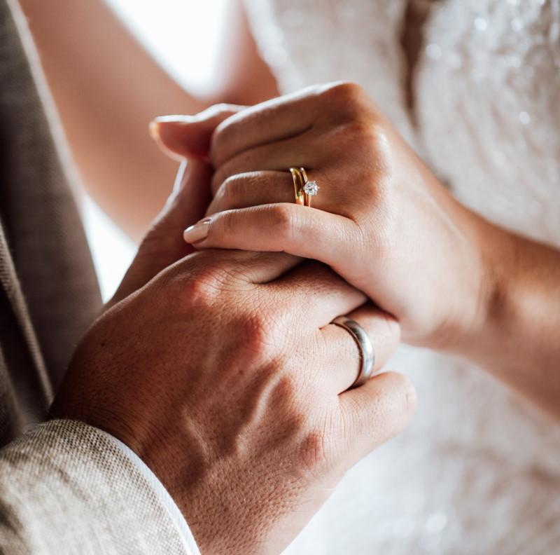 Ζεύγος σε γάμω με μονόπετρο δαχτυλίδι και βέρα
